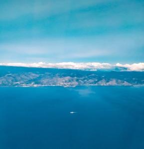 Posto finestrino sul volo milano malpensa - catania. una distesa d'acqua e un paesaggio mozzafiato