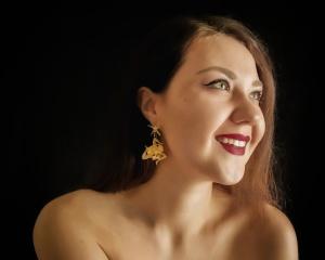 ritratto ragazza con orecchini a forma di trinacria, sicilia